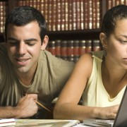 Young couple study together in an office with many books and a computer. Horizontally framed photo.